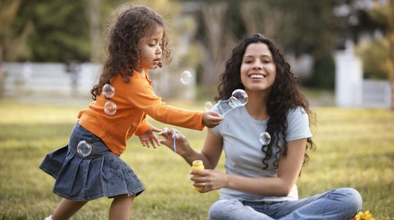 Mother and daughter playing with bubbles