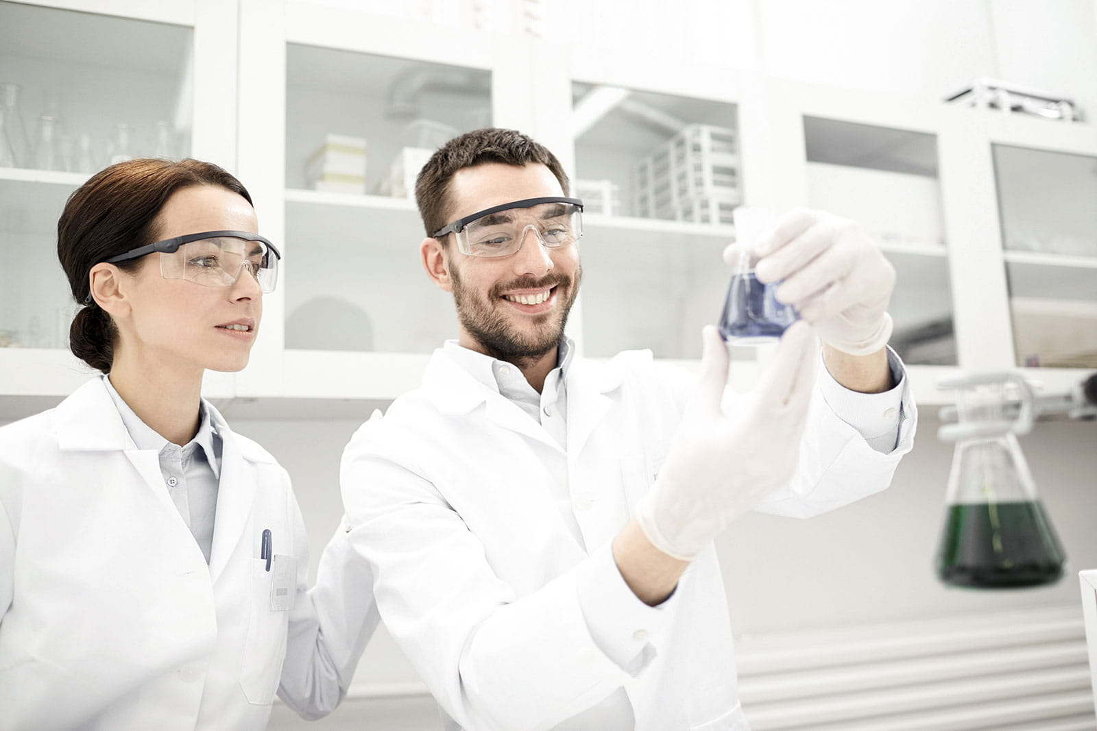 Female and male researchers in a lab holding beaker